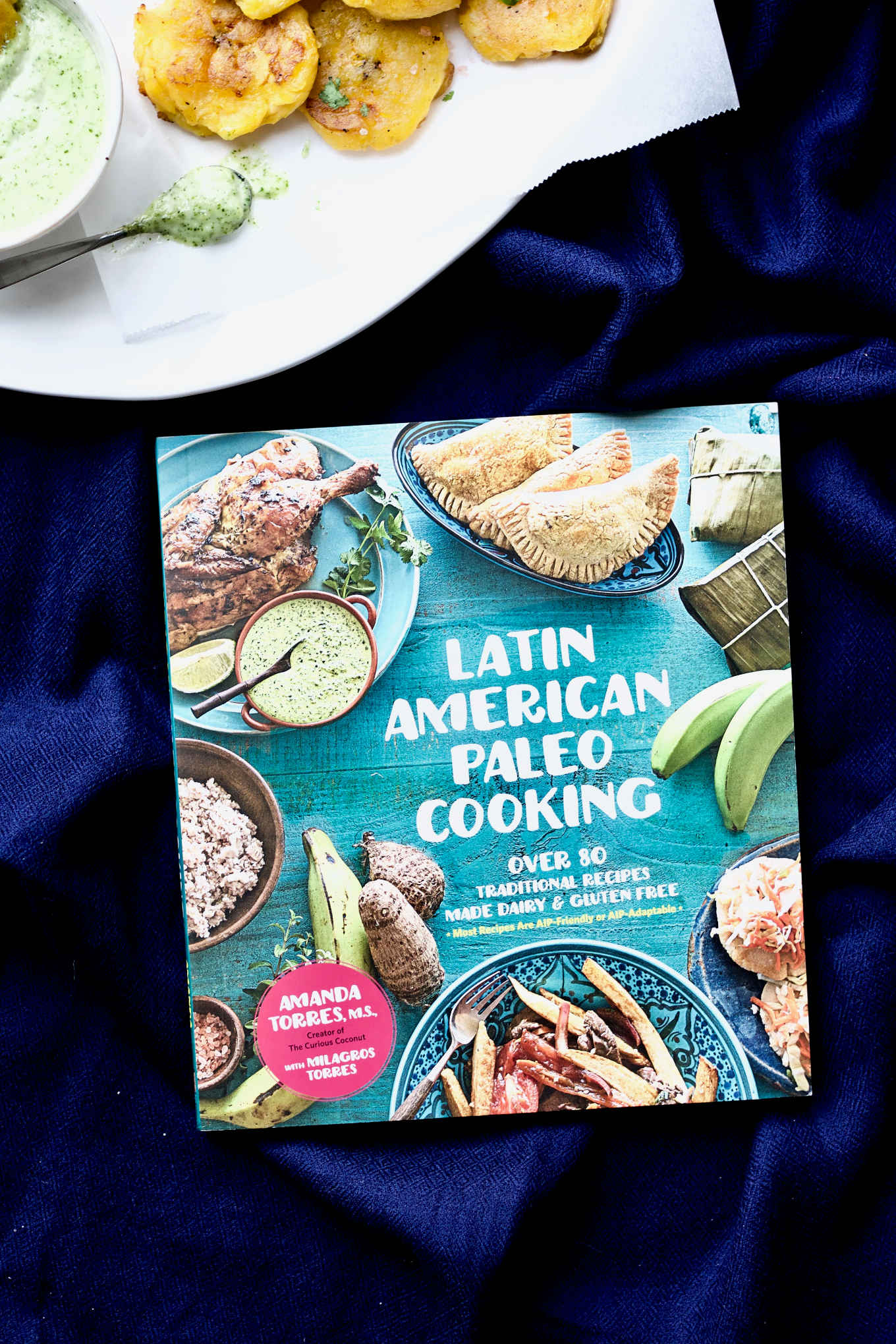 "The ""Latin American Paleo Cooking"" cookbook resting beside a plate of tostones served with garlic cilantro mayo."