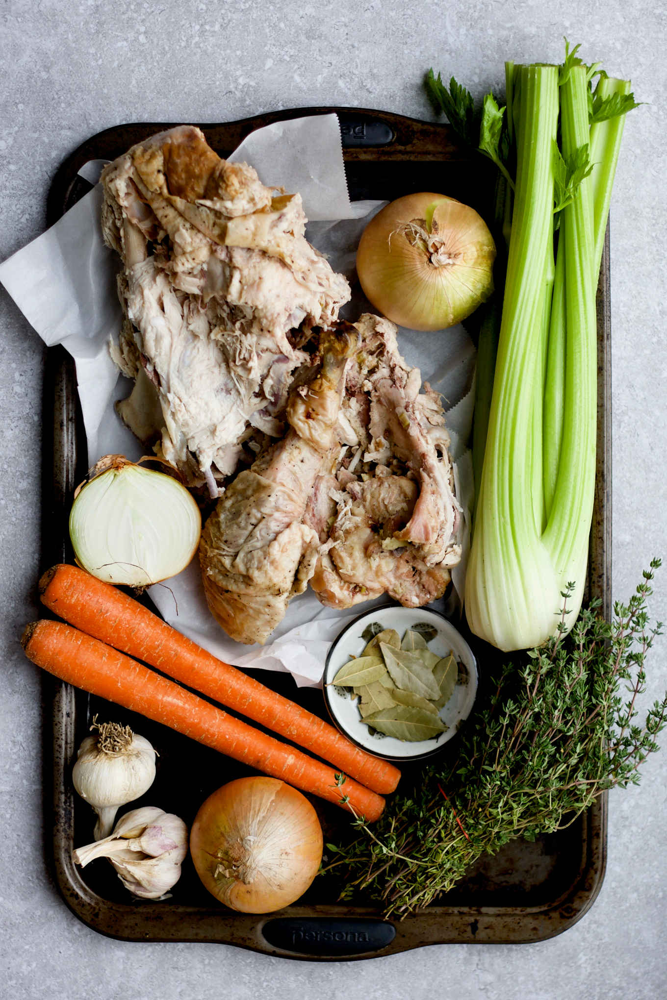 Ingredients for turkey carcass broth in a tray: roasted turkey carcass, celery, onion, carrots, garlic, bay leaf, thyme.