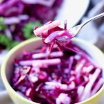 Purple cabbage and jicama slaw picked up with a folk.