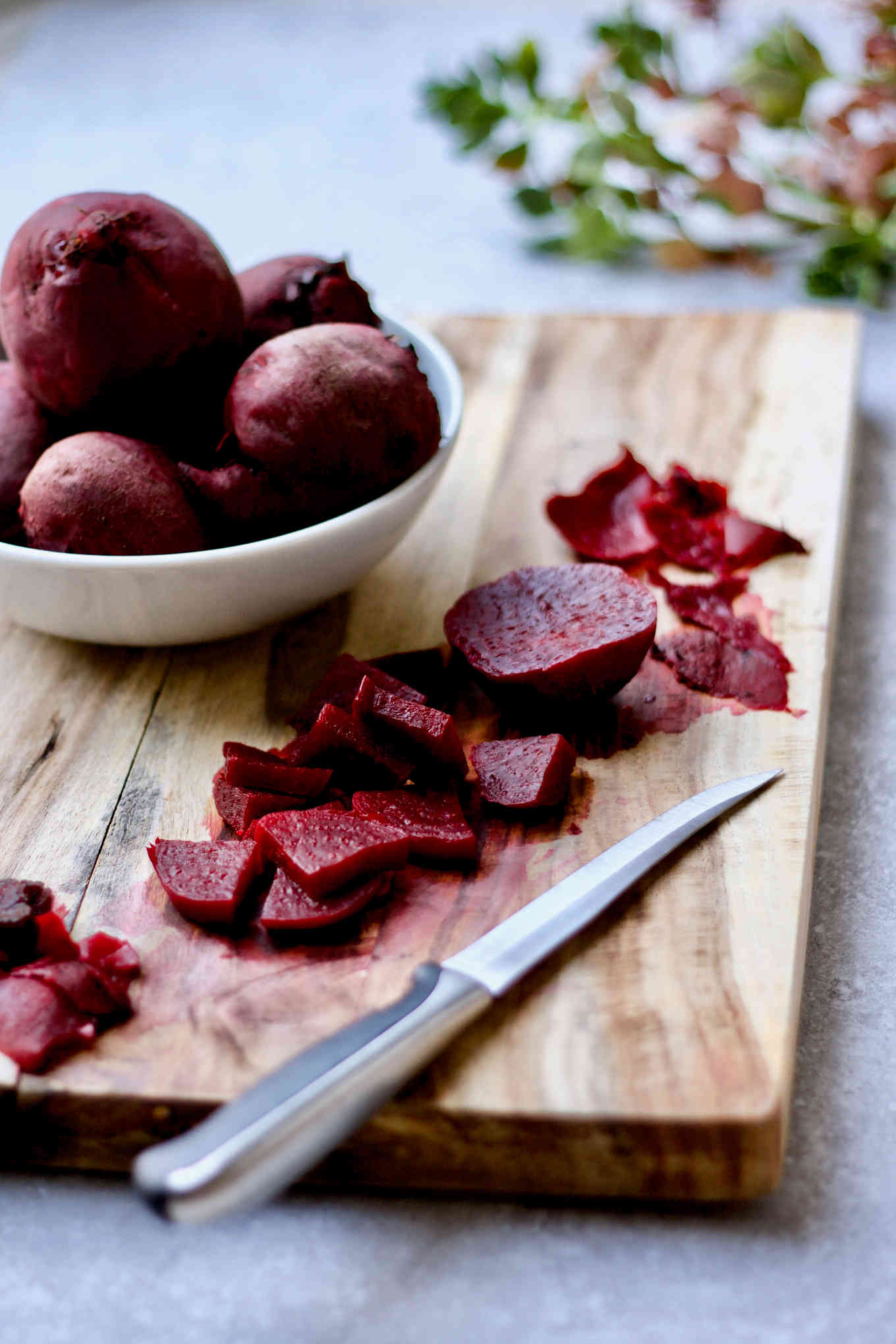 Instant Pot cooked beets in a bowl. Some beets have skin removed and cut into smaller pieces on the cutting board.