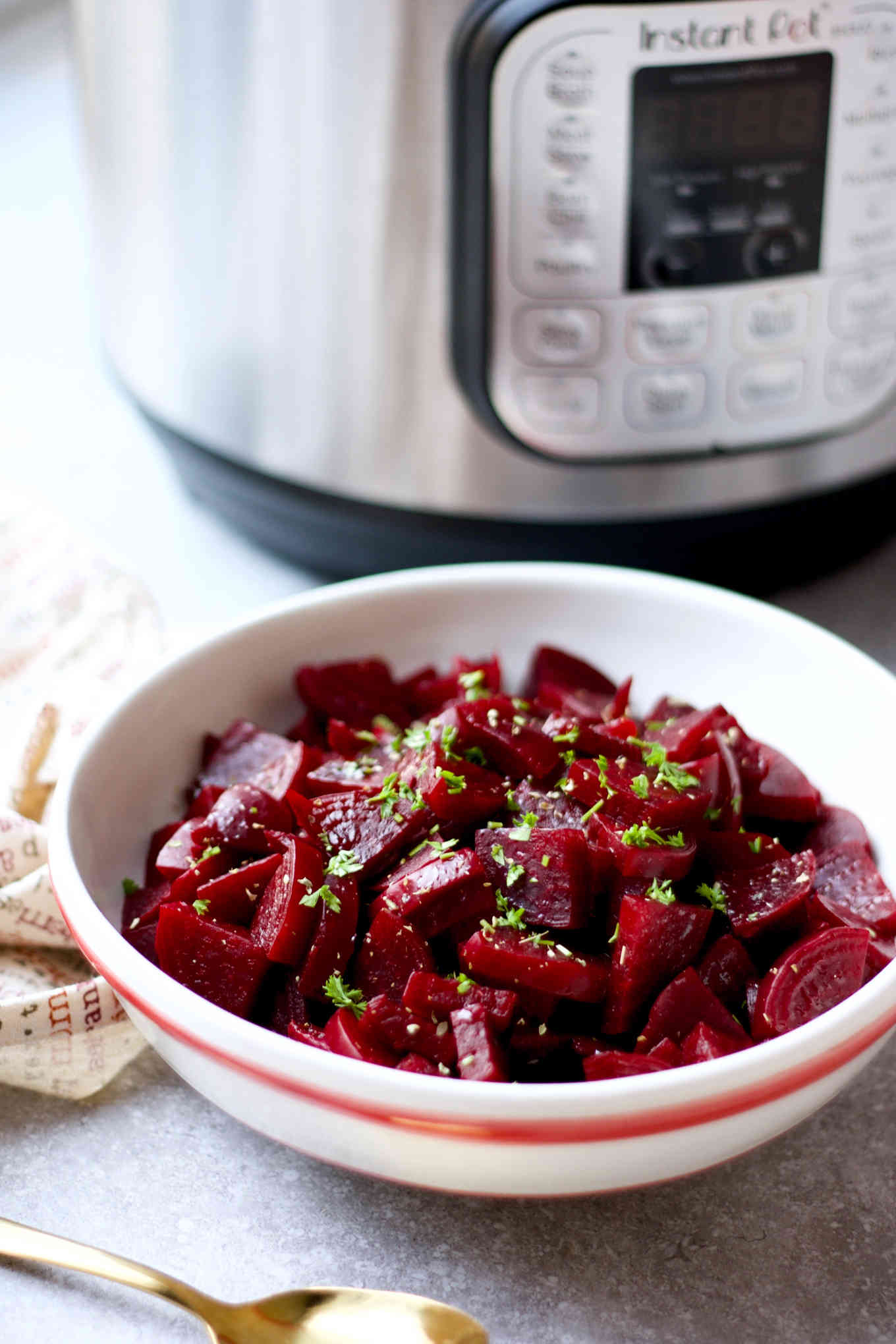 A bowl of beets salad in front of an Instant Pot.