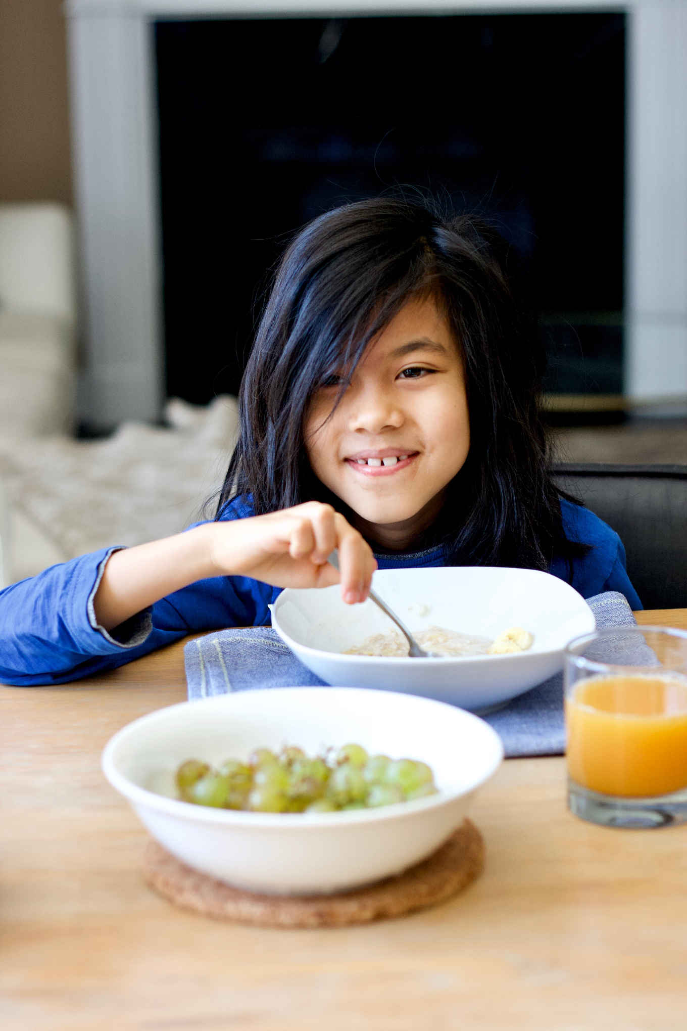 a young child eating oatmeal and banana on the morning of the liver detox day