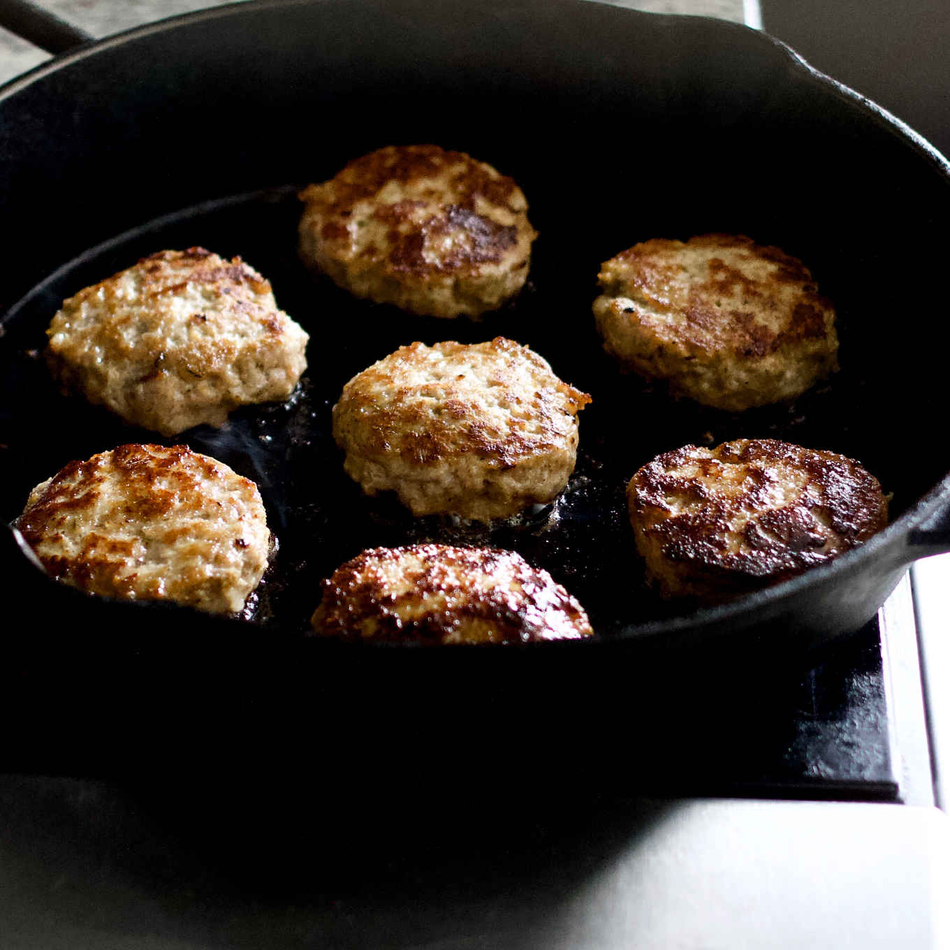 cooking breakfast sausage patties in cast iron skillet