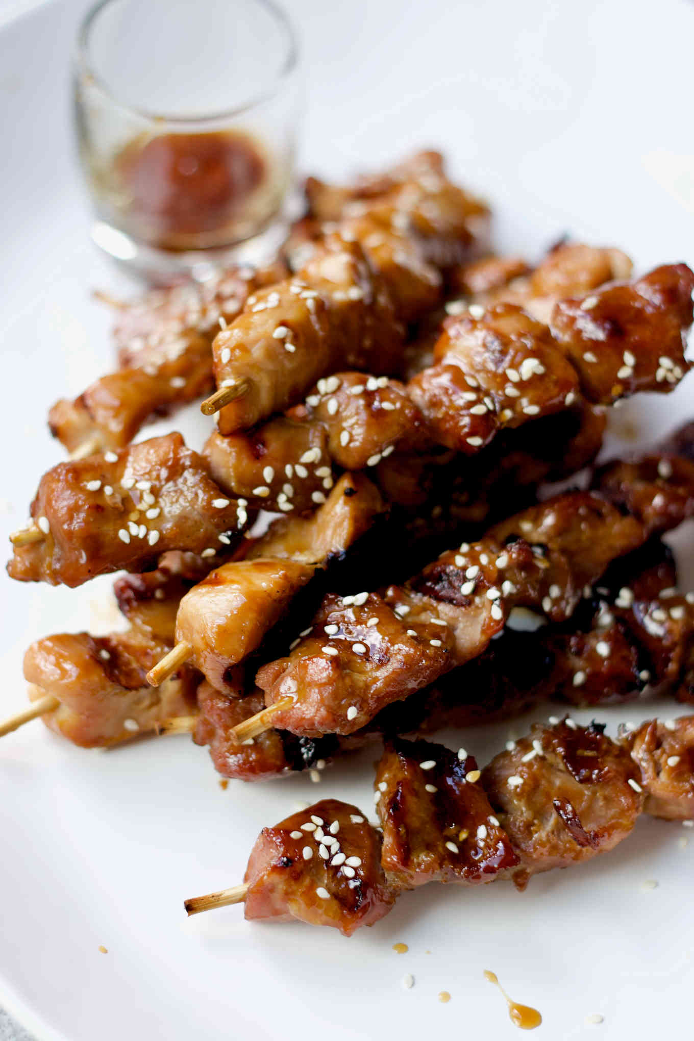 Japanese grilled turkey skewers with beautiful grill marks and sticky glaze decorated with sesame seeds.