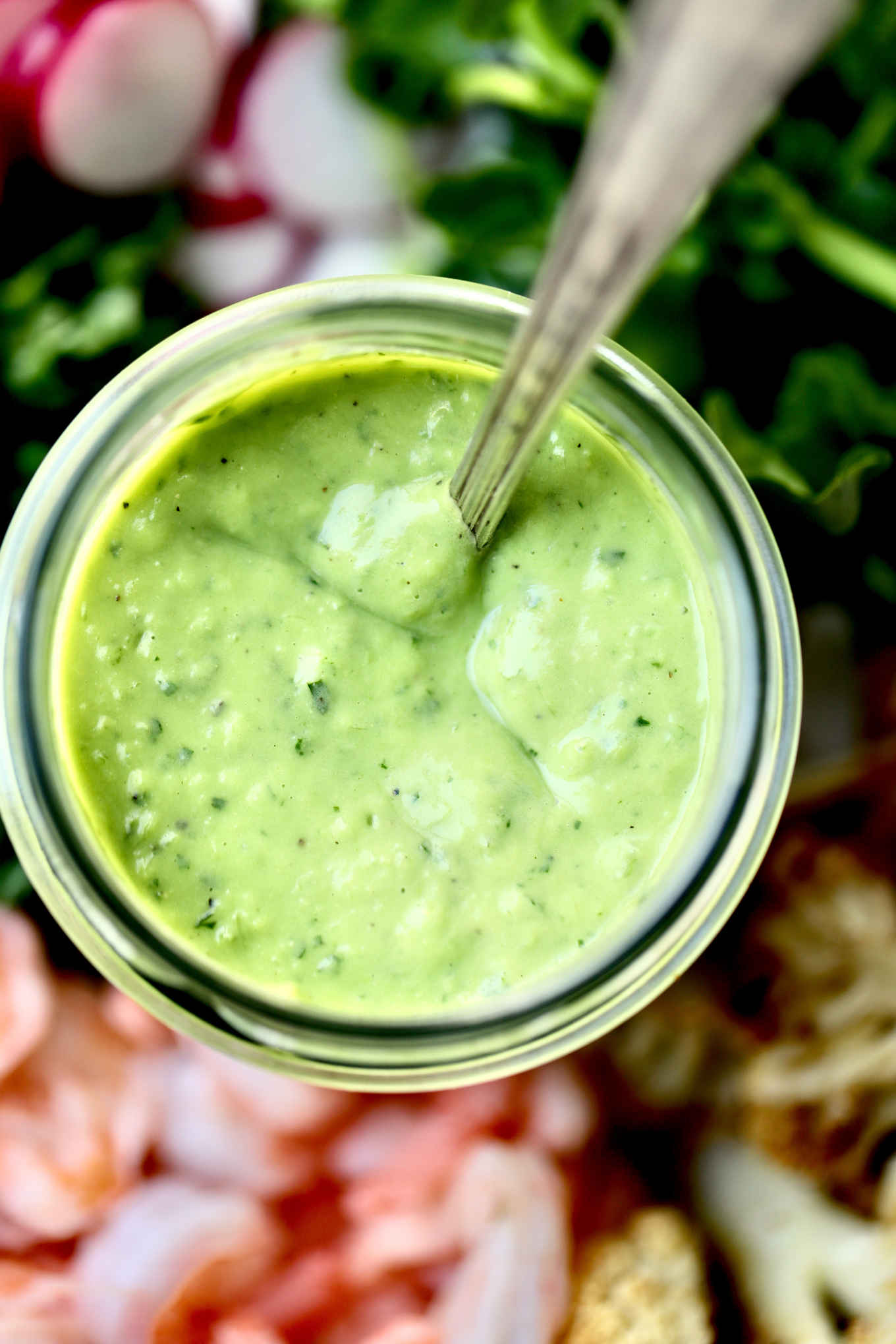 avocado green goddess dressing served on a salad platter of salad greens, cooked shrimps and roasted vegetables
