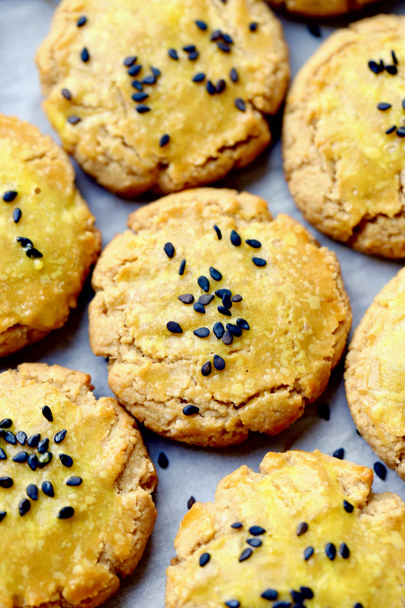 a closeup of buttery, crumbly, moist, light and nutty sorghum almond cookies, topped with a shiny egg glaze and black sesame seeds