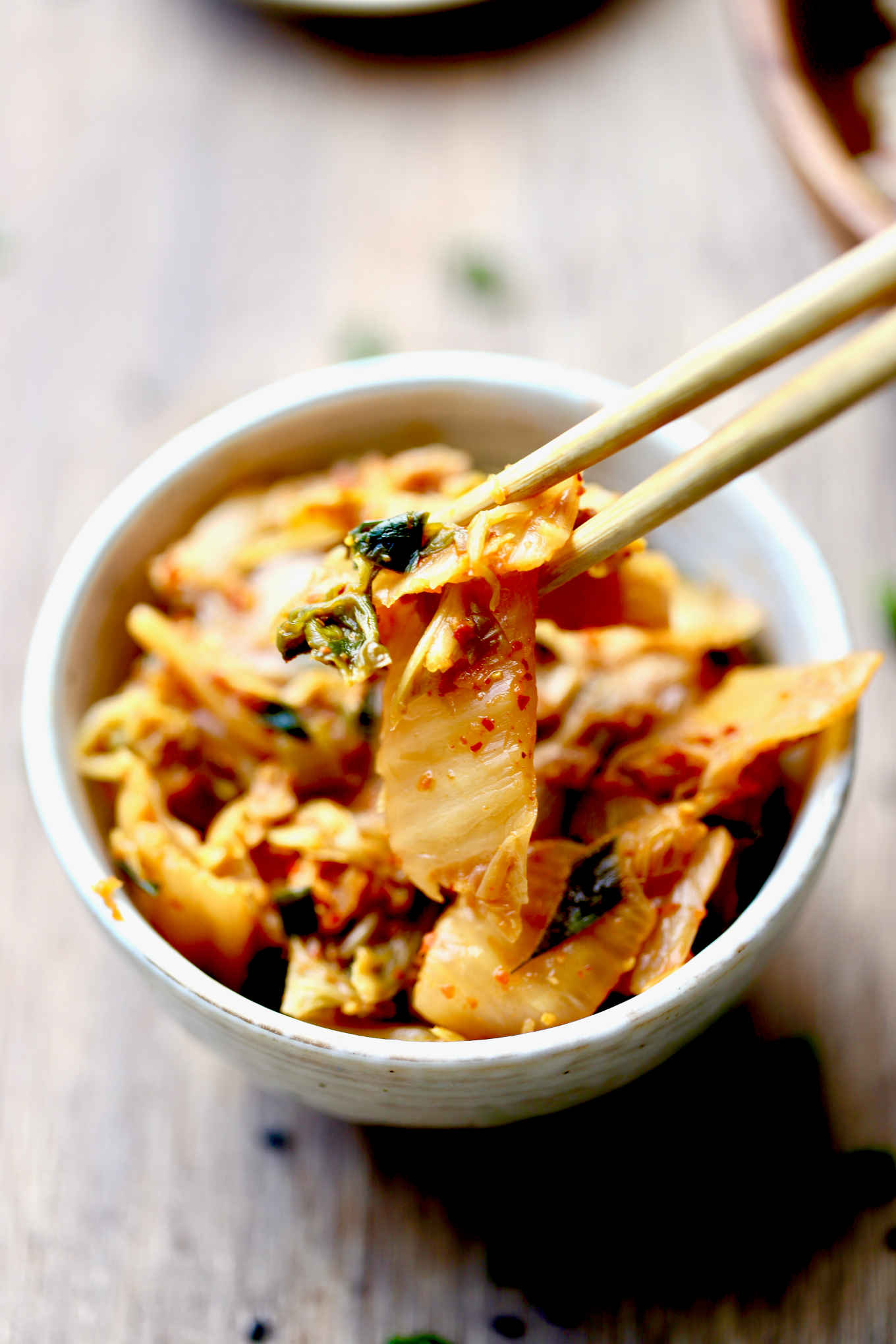 a pair of chopsticks picking up kimchi from a bowl. this recipe is keto, paleo, GAPS of whole 30.