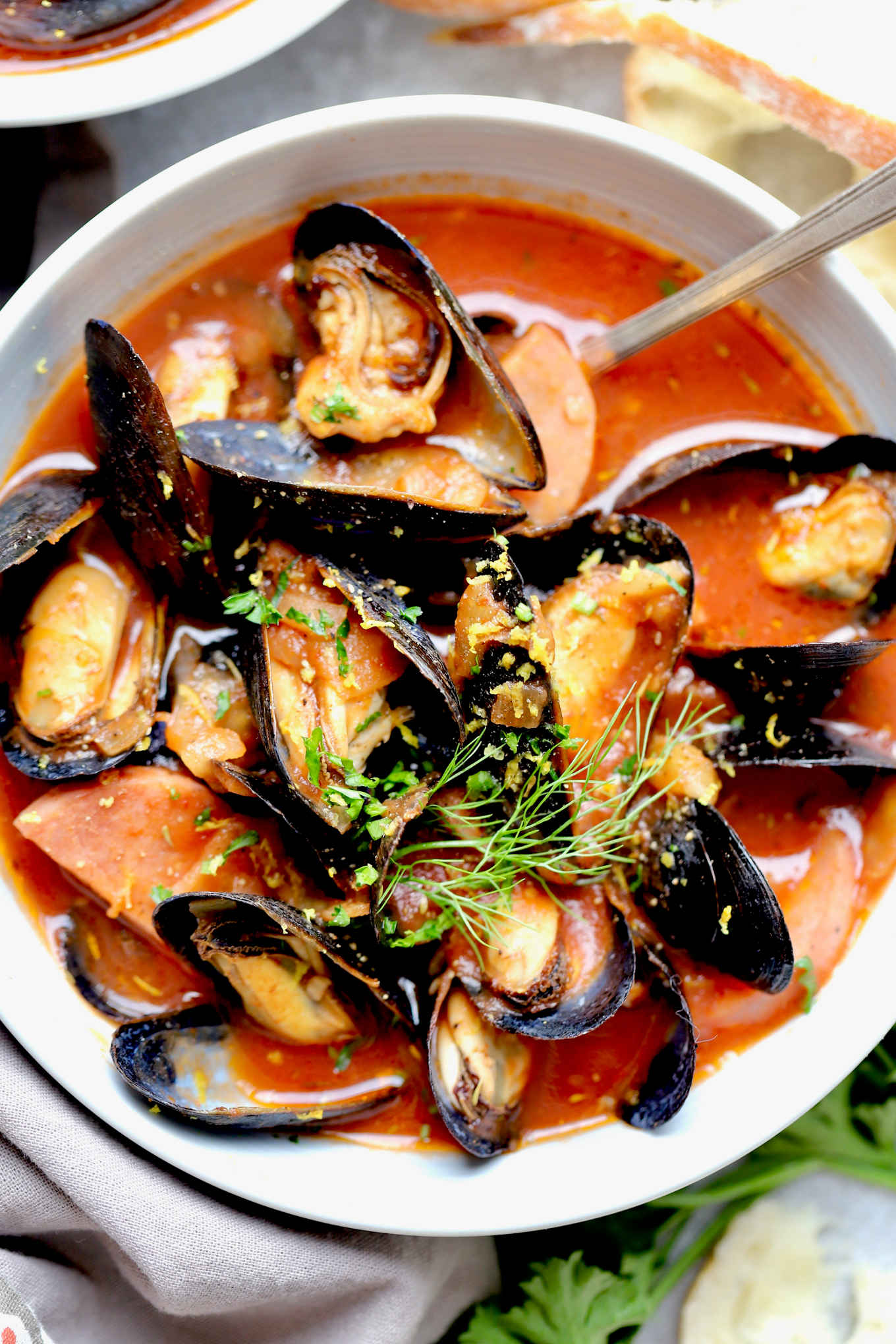 A closeup shot of sausage and mussels in tomato broth, topped with generous amount of fresh herbs and lemon zest.