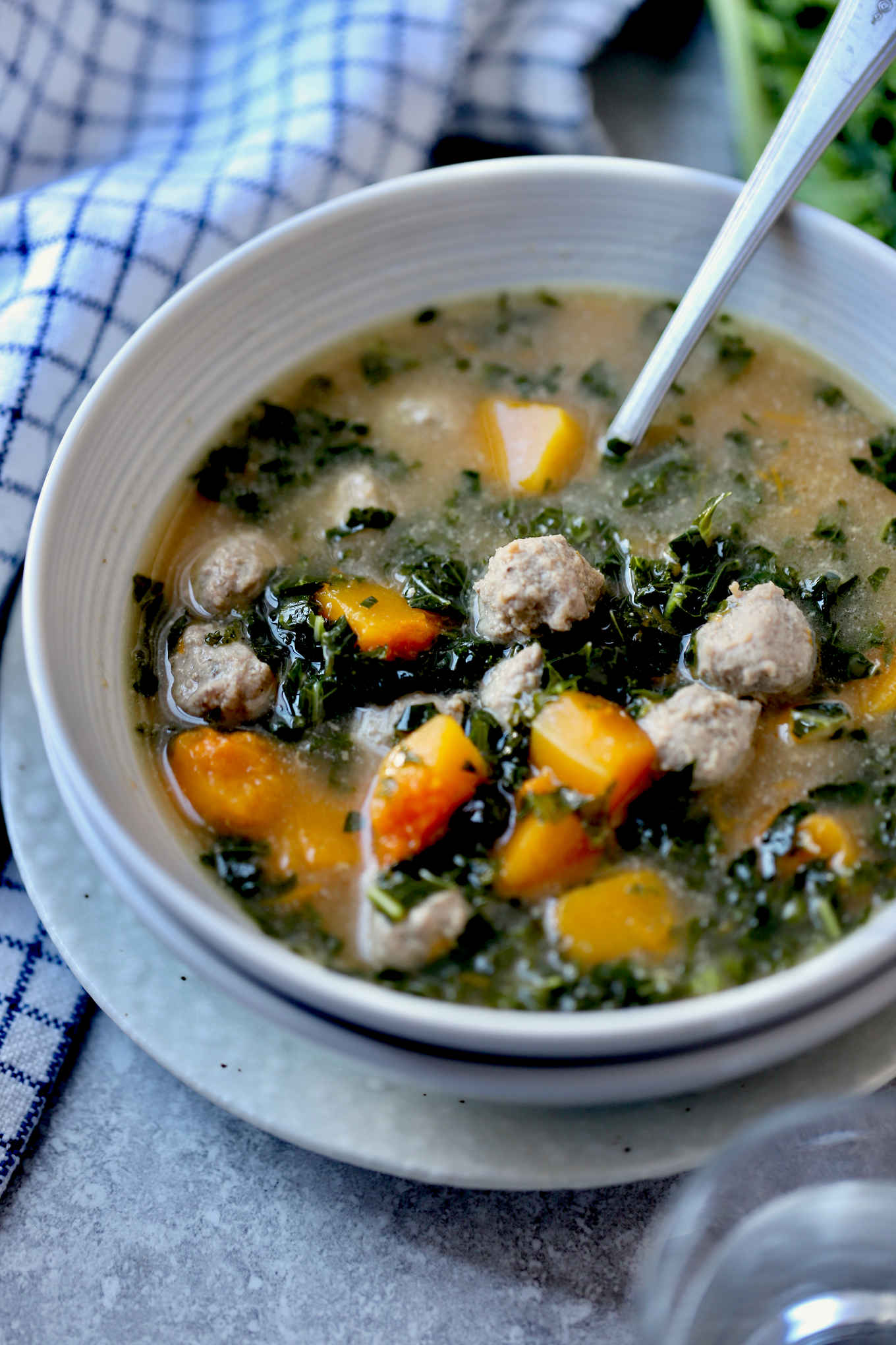 winter squash, kale and meatball soup in a bowl